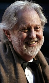 A profile image of David Puttnam. An older Caucasian male with shoulder-length white hair and a short white beard. The man is shown from his front-right profile, facing right and smiling away from the camera.
