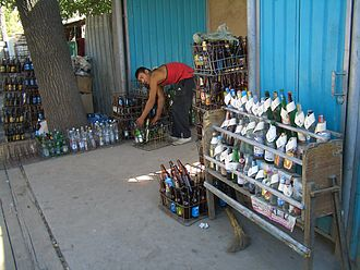 Container deposit legislation - Refillable glass bottles collected, and deposits refunded, at a collection point in Bishkek, Kyrgyzstan. Deposit values (from 50 tyiyn to 2 Kyrgyz som, i.e. 2–5 U.S. cents) for various bottle types are posted next to the sample bottles on a rack.