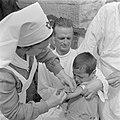 Een kind krijgt in een polikliniek van een vrouwelijke verpleegkundige van de me, Bestanddeelnr 255-0952.jpg
