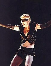 Madonna wearing black shorts and looking to her right. Her arms are open and a headset microphone to her mouth.[19]
