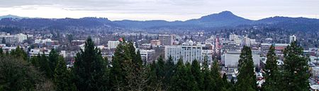 The flat-roofed buildings of downtown Eugene in front of Spencer Butte, a prominent forested hill