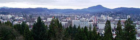 La plat-superkovritaj konstruaĵoj de la centra Eugene antaŭ Spencer Butte, elstara arbarkovrita monteto