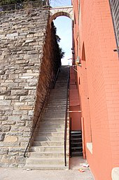 A long steep staircase with a stone wall on the left and a painted red brick wall on the right.