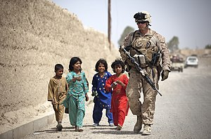 War in Afghanistan order of battle, 2012 - An ISAF Marine walking alongside Afghan children in Afghanistan's Helmand Province in April 2012.