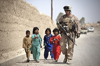 War in Afghanistan order of battle, 2012 - An ISAF Marine walking alongside Afghan children in Afghanistan's Helmand Province in April 2012.