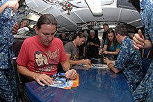 Two men signing autographs in a crowded submarine