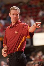 Fred Hoiberg in a red Iowa State polo shirt tucked into black pants