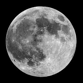 Full moon in the darkness of the night sky. It is patterned with a mix of light-tone regions and darker, irregular blotches, and scattered with varying sizes of impact craters, circles surrounded by out-thrown rays of bright ejecta.
