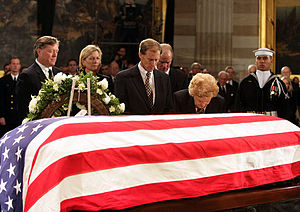 Death and state funeral of Gerald Ford - Betty Ford kneels in prayer at the casket of her late husband, Gerald Ford, as he lies in state. The Ford children, left to right, are Jack, Susan, Michael, and Steven.