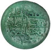 The obverse of a bluish green-colored glass piece inscribed in Arabic