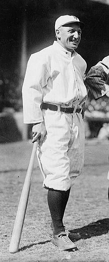 A smiling man wearing an old-style white baseball uniform and cap, standing on a baseball field and leaning on a baseball bat