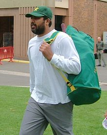A beard man wearing a green cricket cap and a white shirt with a bag on his back.