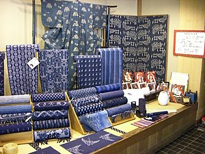 A display table diaplaying a number of different indigo-dyed kasuri fabrics. A number of fabrics are displayed stacked on wooden stands in roll-form, displaying a variety of different patterns and colours ranging from the lightest blue to the deepest indigo. A small length of kasuri is displayed flat in front of the rolls; it shows a woven design of swallows or plovers. Behind the rolls of fabric, four different types of kasuri are displayed hanging on small stands, showing patterns of stripes and roundels, amongst others. At the very back, a kasuri kimono is displayed, with a small, repeating white pattern on a medium-blue base. Next to it, two large noren curtains dyed a deeper indigo, also using the kasuri technique, are displayed.