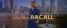 Lauren Bacall with a city skyline in the background with her name at the bottom of the image