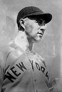 "A black-and-white photo of a man in a white baseball jersey with ""NEW YORK"" across the chest in block letters and a dark baseball cap"