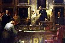 colour a paining of men and women in formal Edwardian dress, standing around (and one woman seated at) a boardroom table