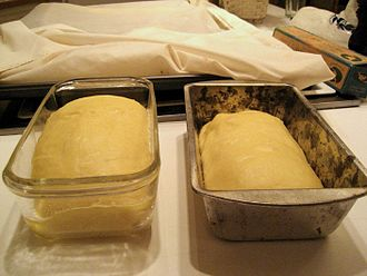 Proofing (baking technique) - Challah proofing in loaf pans.  Bread covered with linen proofing cloth in the background.