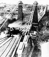 Three railway lines merge into one, crossing a bridge. A train engine has crossed the bridge and is moving into the left-most line.