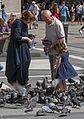 Man, woman, girl and pigeons in Piazza del Duomo, Milan.jpg