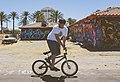 Man riding bike in front of graffiti (Unsplash).jpg