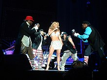 A blonde woman wearing a white top and short skirt sings. She is flanked by four men, who pretend to take photographs of her.