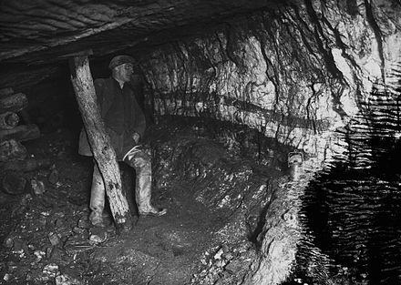 A miner underground at Pumsaint gold mine, Wales; c. 1938. Miner underground at Pumsaint gold mine (1294028).jpg