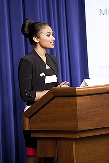 Davuluri standing at a podium