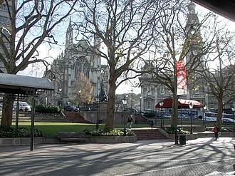 The Octagon, Dunedin - The Octagon, looking towards St. Paul's Cathedral (left) and the Municipal Chambers (Dunedin Town Hall) (right). The Robert Burns statue is visible in front of the cathedral.