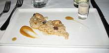 Two oysters and a handful of raisins rest atop a line of oatmeal. On either side is a streak of maple syrup. The dish is served on a white tray.