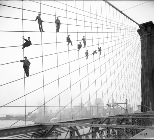 Painters suspended on cables of the Brooklyn Bridge, on 07 October 1914