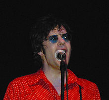 Shoulder high portrait wearing red polka dot shirt and blue sunglasses, sweating, singing into microphone which partly hides his face.