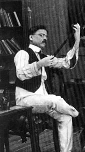 Dadasaheb Phalke, examining a strip of film