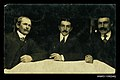 Photographic postcard of three men with moustaches sitting around a table (10413349285).jpg