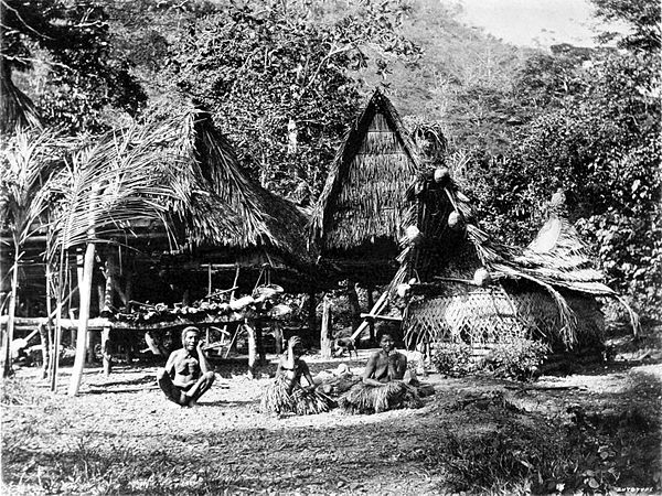 Black and white photograph of a village of huts in a wooded area.  Three people sit in the foreground.