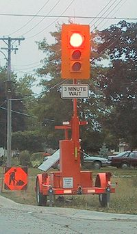 Portable, Solar Powered, Traffic Light used when construction workers must narrow a 2way street to a single lane and must emplace traffic controls for safety.