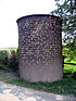 A cylindrical brick structure standing by a footpath.