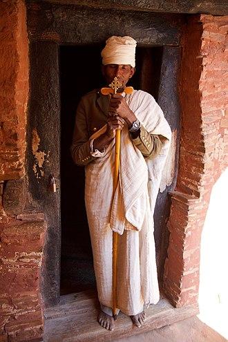 Abuna Yemata Guh - Priest holding the hand cross at church entrance