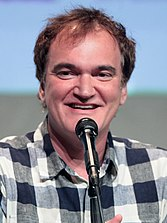 A smiling Quentin Tarantino dressed in a casual shirt speaking into a microphone