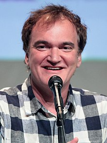 A photograph of Quentin Tarantino, speaking to the press.