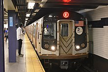 The front end of a subway train, with a red E on a LED display on the top. To the left of the train is a platform with a person walking away.