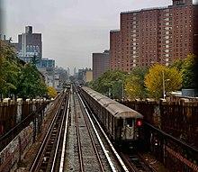 Un train 1, composé ici de voitures R62A est vu au-dessus du sol à l'approche de la gare de la 125th Street.  L'arrière du train contient deux feux blancs fournissant un léger éclairage, deux fenêtres, une porte et le symbole de la ligne 1 sur la fenêtre de gauche.
