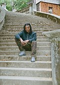 Rapper Myl3z sits on a step on Orchard Lane in Berkeley - July - 2019.jpg