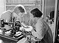 Renée (links) en Hans achter een naaimachine Hans stift haar lippen, Bestanddeelnr 255-8767.jpg