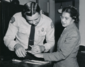 Rosa Parks being fingerprinted by Deputy Sheriff D.H. Lackey after being arrested on February 22, 1956, during the Montgomery bus boycott.png