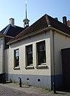 foto van Gepleisterd pand zonder verdieping, met pannen schilddak, achter het voormalige raadhuis