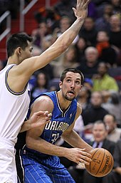 "A basketball player, wearing a blue jersey with the word ""ORLANDO"" and the number 33 on the front, with the basketball and being guarded by a player who has his right arm extended."