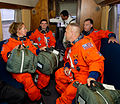 STS-135 crew grab their bags on shuttle.jpg