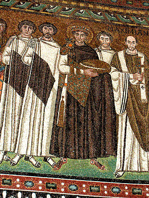 Byzantine dress - Mosaic from the San Vitale church in Ravenna. Few later emperors would dress so simply as in a mosaic as Justinian I here, though his dress is far richer at every point than his attendants. He and they have the tablion diagonally across their torsos. This bishop probably wore this style of dress, which is very close to modern church vestments, for most of the time. Note what appears to be shoes and socks.