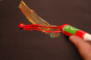 Red paint tube is squeezed by hand over previous line of paint on dark border.