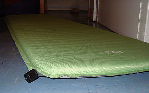 Sleeping pad - An example of a 183x51x3.8 cm self-inflating mattress, made from diamond ripstop. The black high volume valve can be seen in the left foreground.